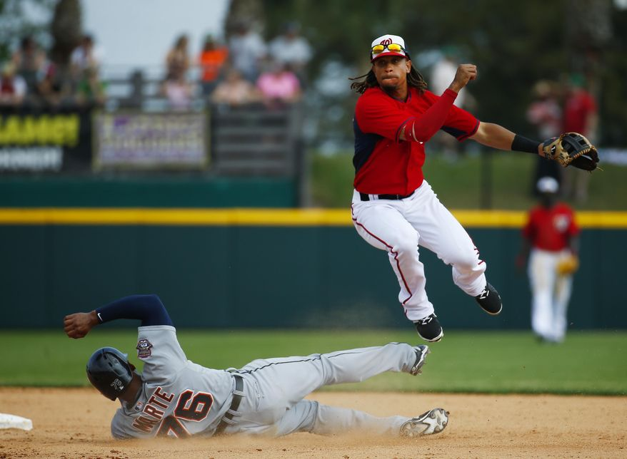 Washington Nationals shortstop Emmanuel Burriss (16) avoids Detroit Tigers' Jefry Marte (76) as he turns a double play on a  Steven Moya ground ball in the 10th inning of an exhibition spring training baseball game  Thursday, March 19, 2015, in Viera, Fla.  The game ended in a scoreless tie. (AP Photo/John Bazemore)