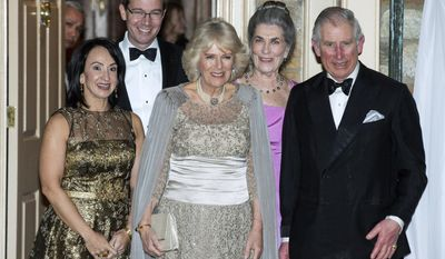 Britain's Prince Charles and his wife Camilla, the Duchess of Cornwall, are joined by Elena Allbritton, left, Robert Allbritton, second from left, and Barby Allbritton as they arrive for a reception in Washington, March 18, 2015. (AP Photo/Joshua Roberts, Pool)