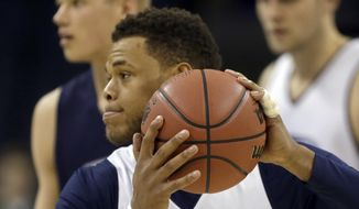 Virginia's Justin Anderson runs a drill with his injured finger taped during practice at the NCAA college basketball tournament in Charlotte, N.C., Thursday, March 19, 2015.  Virginia plays Belmont in the second round on Friday. (AP Photo/Gerald Herbert)