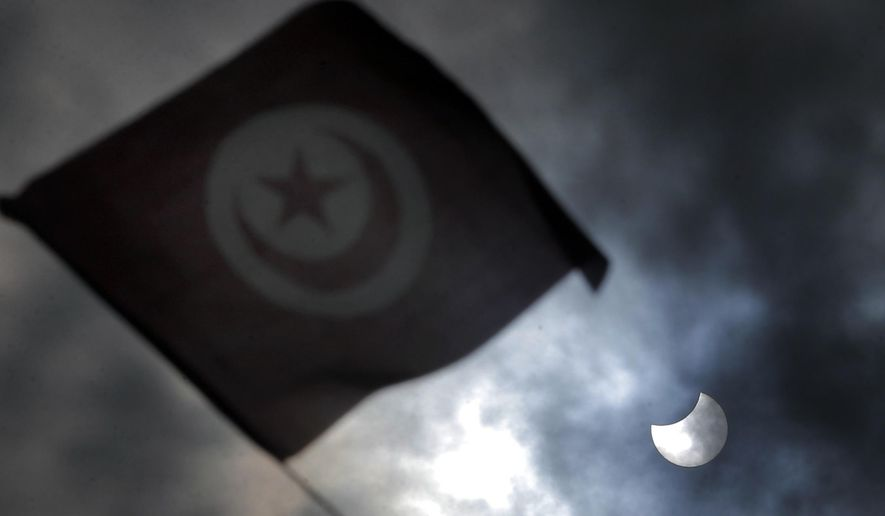 The Tunisian flag flies as the sun is seen during an eclipse in Tunis, Tunisia, Friday, March 20, 2015. An eclipse is darkening parts of the world on Friday in a rare solar event that won't be repeated for more than a decade. (AP Photo/Christophe Ena)