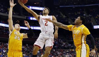 Maryland's Melo Trimble shoots between Valparaiso's Alec Peters (25) and Darien Walker in the first half of an NCAA tournament college basketball game in the Round of 64 in Columbus, Ohio Friday, March 20, 2015. (AP Photo/Paul Vernon)