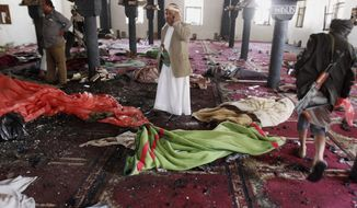 People stand amid bodies covered with blankets in a mosque after a suicide attack during the noon prayer in Sanaa, Yemen, Friday, March 20, 2015. (AP Photo/Hani Mohammed)
