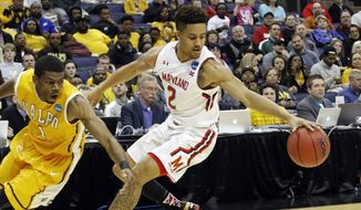 Maryland's Melo Trimble (2) controls the ball against Valparaiso's E. Victor Nickerson (1) in the second half of an NCAA tournament college basketball game in the Round of 64 in Columbus, Ohio, Friday, March 20, 2015. (AP Photo/Paul Vernon)