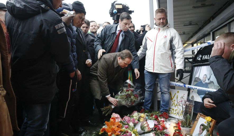 Swedish Prime Minister Stefan Lofven places a flower tribute at the scene of a Wednesday fatal shooting in Gothenburg, western Sweden Friday March 20, 2015.  Two people were killed and several injured when at least one gunman opened fire with automatic weapons into a pub,  in Gothenburg, in what the police described as a gang related assault. (AP Photo/Bjorn Larsson Rosvall, TT News Agency)  SWEDEN OUT