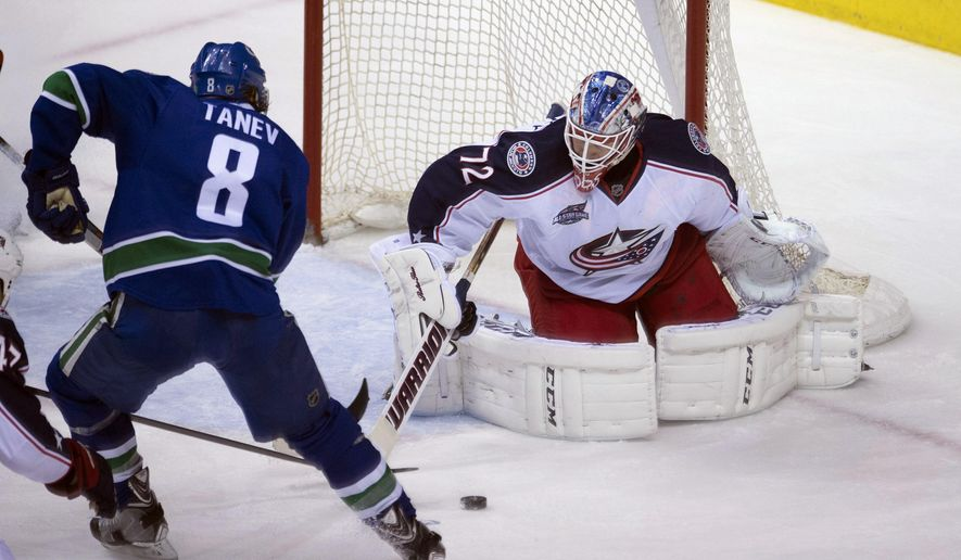 Vancouver Canucks defenseman Chris Tanev (8) tries to get a shot past Columbus Blue Jackets goalie Sergei Bobrovsky (72) during the second period of an NHL hockey game in Vancouver, British Columbia, Thursday, March. 19, 2015. (AP Photo/The Canadian Press, Jonathan Hayward)