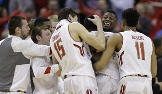 Maryland's Jonathan Graham, back right, celebrates with teammates after an NCAA tournament college basketball game against Valparaiso in the Round of 64, Friday, March 20, 2015, in Columbus, Ohio. Maryland won 65-62. (AP Photo/Tony Dejak)