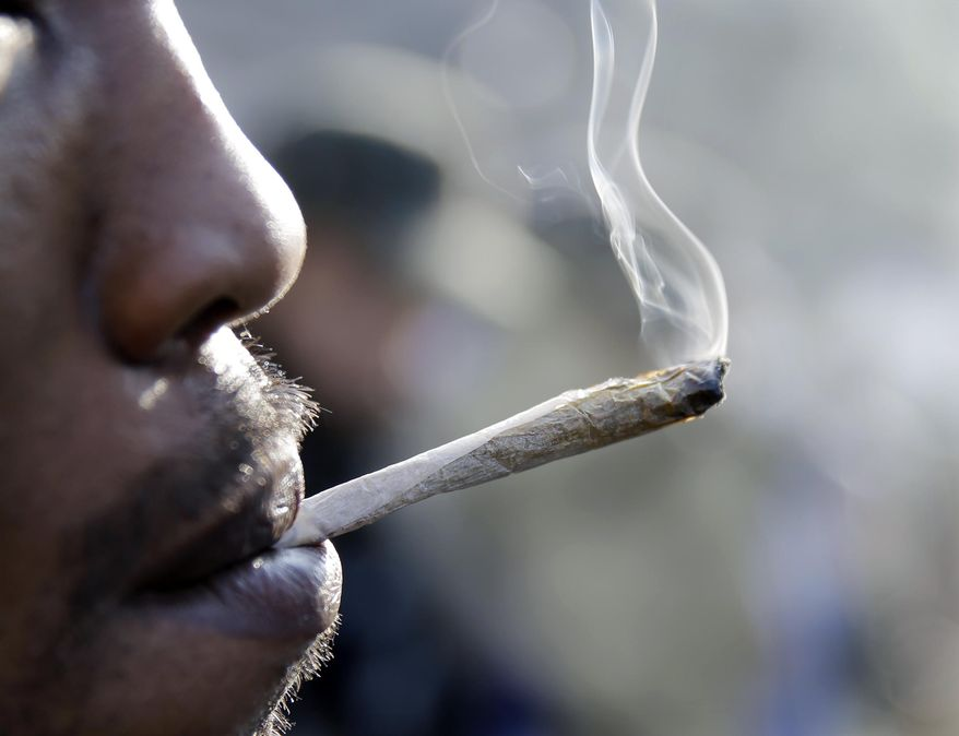 A man smokes a marijuana cigarette as a large group gathered near the New Jersey Statehouse to show their support for legalizing marijuana Saturday, March 21, 2015, in Trenton, N.J. The event drew a diverse crowd of roughly 200 people. Many said they wanted to show their support for legalizing or decriminalizing pot, while others said it should only be given to people with medical conditions that could be eased by the drug. Several people were openly smoking the drug during Saturday's rally, but apparently none were arrested. (AP Photo/Mel Evans)