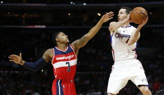 Los Angeles Clippers' J.J. Redick, right, passes the ball as Washington Wizards' Bradley Beal, left, defends against him during the first half of an NBA basketball game, Friday, March 20, 2015, in Los Angeles. (AP Photo/Danny Moloshok)