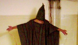 This late 2003 file image obtained by The Associated Press shows an unidentified detainee standing on a box with a bag on his head and wires attached to him at the Abu Ghraib prison in Baghdad, Iraq. (AP Photo/File)