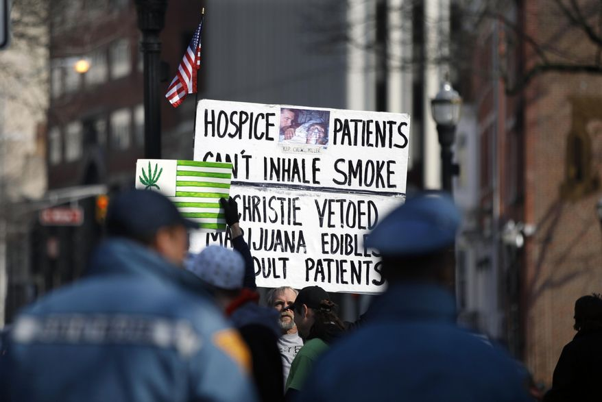 New Jersey State Police watch as several people hold signs during a large gathering near the New Jersey Statehouse to show their support for legalizing marijuana Saturday, March 21, 2015, in Trenton, N.J. (AP Photo/Mel Evans) **FILE**