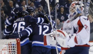 Winnipeg Jets celebrate Mark Scheifele's (55) goal against Washington Capitals goaltender Braden Holtby (70) during second-period NHL hockey game action in Winnipeg, Manitoba, Saturday, March 21, 2015. (AP Photo/The Canadian Press, John Woods)