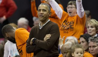 President Barack Obama, center, watches the player's introductions of the Princeton vs Green Bay women's college basketball game in the first round of the NCAA tournament in College Park, Md., Saturday, March 21, 2015. Obama's niece Leslie Robinson, plays for Princeton. (AP Photo/Pablo Martinez Monsivais)