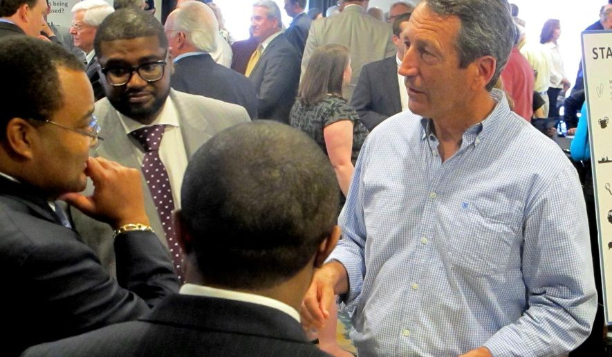 In a March 11, 2015 photo, U.S. Rep. Mark Sanford, R-S.C., right, speaks to attendees at a meeting of the federal  Bureau of Ocean Energy Management in Mount Pleasant, S.C., to take public comment on opening areas off the Atlantic  coast to drilling for oil and natural gas. The views of the five coastal congressmen in the Carolinas vary on the issue in states where the governors are advocates for offshore drilling but 18 coastal communities have gone on record against it.  (AP Photo/Bruce Smith)