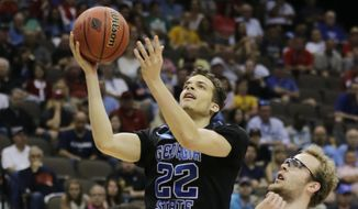 Georgia State guard R.J. Hunter (22) goes in for a shot between Xavier's Dee Davis, left, and Xavier's Matt Stainbrook during the first half of an NCAA tournament third round college basketball game, Saturday, March 21, 2015, in Jacksonville, Fla. (AP Photo/Chris O'Meara)