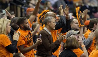 President Barack Obama, center, with his nephew Avery Robinson, left, and brother-in-law Craig Robinson, right, standup and join other fans in the final minute of Princeton vs Wisconsin-Green Bay women's college basketball game in the first round of the NCAA tournament in College Park, Md., Saturday, March 21, 2015. Obama's niece Leslie Robinson, plays for Princeton, and advances to the next round after winning 80-70. (AP Photo/Pablo Martinez Monsivais)