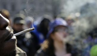 People smoke marijuana cigarettes as a large group gathered near the New Jersey Statehouse to show their support for legalizing marijuana Saturday, March 21, 2015, in Trenton, N.J. (AP Photo/Mel Evans)