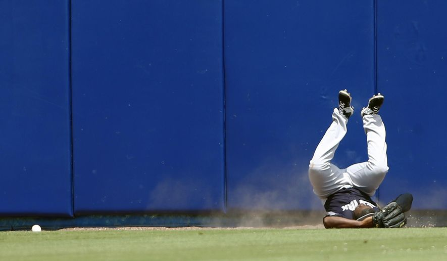 New York Yankees center fielder Jose Pirela rolls on the turf after crashing into the wall while chasing a ball hit for an inside-the-park home run by New York Mets' Juan Lagares in the first inning of an exhibition spring training baseball game Sunday, March 22, 2015, in Port St. Lucie, Fla. Pirela  left the stadium in an ambulance. (AP Photo/John Bazemore)