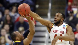 Maryland's Dez Wells (44) blocks a shot by West Virginia's Jevon Carter (2) in the second half of an NCAA tournament college basketball game in the Round of 32 in Columbus, Ohio, Sunday, March 22, 2015. (AP Photo/Paul Vernon)