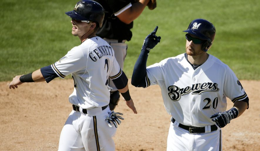 Milwaukee Brewers' Jonathan Lucroy, right, celebrates his two-run home run with teammate Scooter Gennett during the fifth inning of a spring training baseball exhibition game against the Chicago White Sox in Phoenix, Sunday, March 22, 2015. (AP Photo/Chris Carlson)