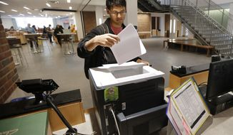 In this Feb. 24, 2015 photo, Vivek Shah, a sophomore resident advisor at Vanderbilt University's Moore College, uses the computer printer in the lobby of the student housing complex in Nashville, Tenn. (AP Photo/Mark Humphrey) **FILE**