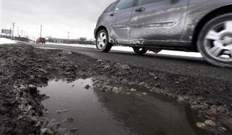 In this Wednesday, Feb. 18, 2015, file photo, a vehicle moves past a large pothole on Oakland Ave in Highland Park, Mich. (AP Photo/Carlos Osorio, File)