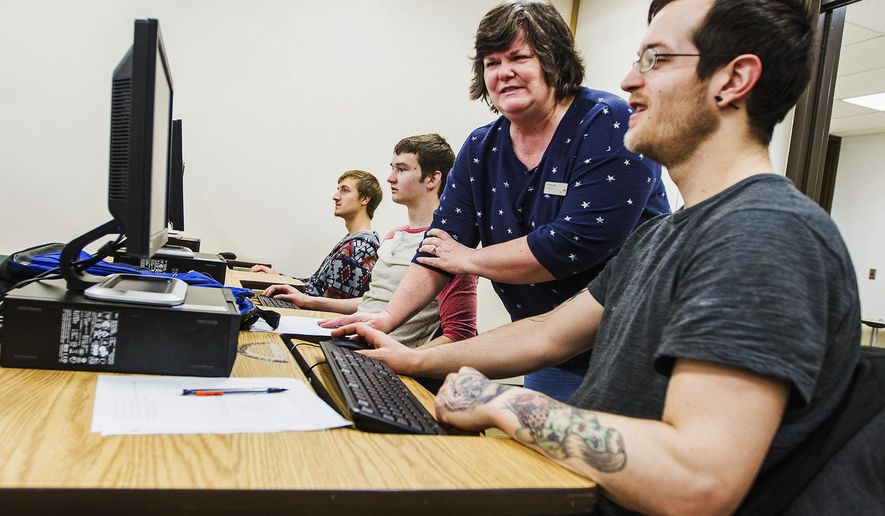 In this Feb. 12, 2015 photo, McHenry County College professor Cynthia Grieb, second from right, works with students from left Aaron Kurowski, left, of McHenry,Ill., Josh Haymond, of Wonder Lake, Ill., and Richard Doocet of Lake in the Hills, Ill., as they work on an assignment during a Applied Logic class in Crystal Lake, Ill. The U.S. Bureau of Statistics predicts that computer science will be the fastest growing industry in the country. Of the 102 schools across Illinois that offer Advanced Placement Computer Science, six are in McHenry County.  (AP Photo/Northwest Herald, Kyle Grillot) CHICAGO TRIBUNE OUT, MANDATORY CREDIT