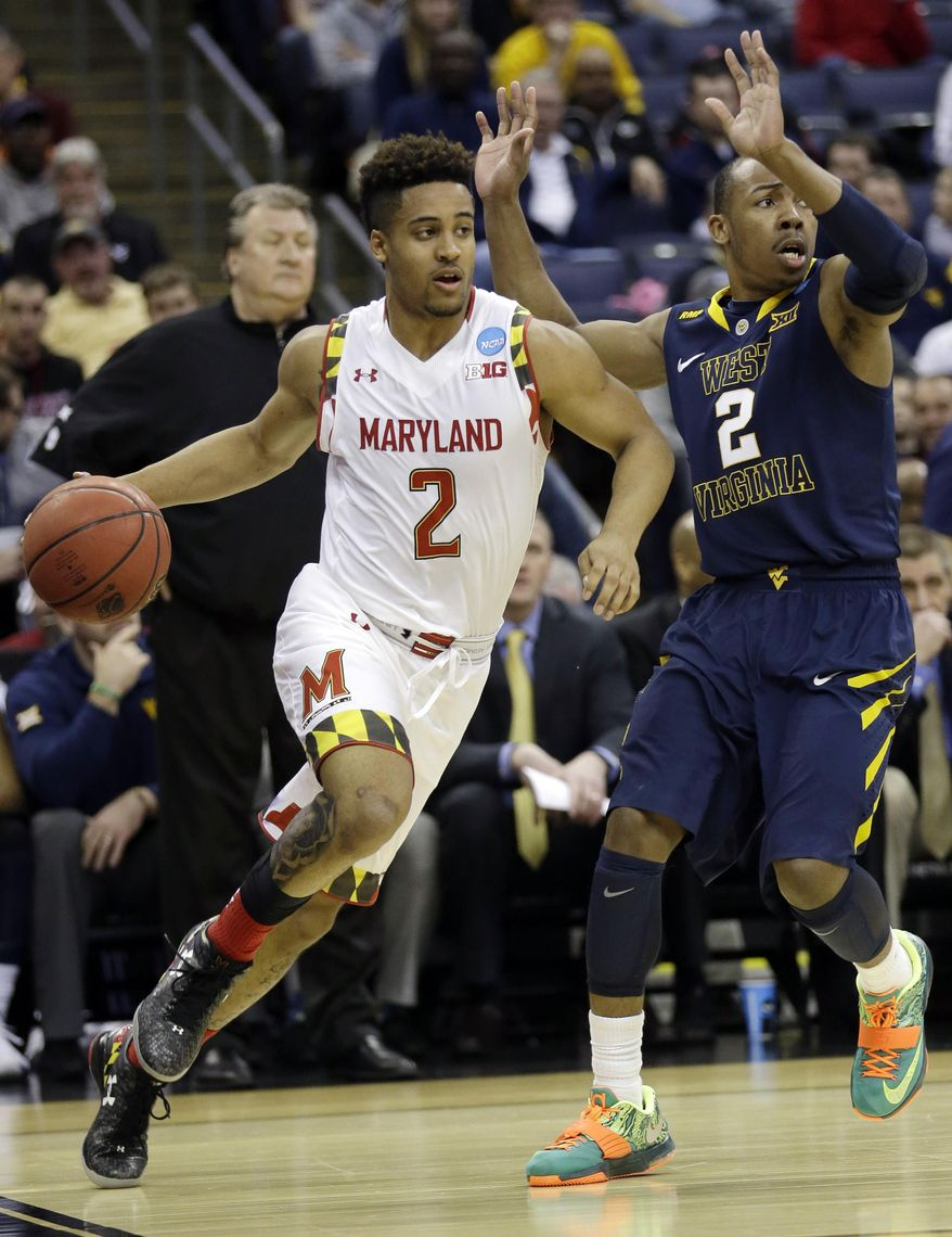 Maryland's Melo Trimble, left, drives against West Virginia's in the first half of an NCAA tournament college basketball game in the Round of 32 in Columbus, Ohio, Sunday, March 22, 2015. (AP Photo/Tony Dejak)