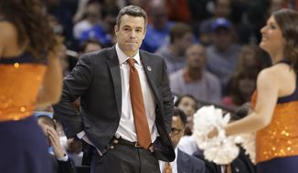 Virginia head coach Tony Bennett looks toward his team during a timeout during the first half of an NCAA tournament college basketball game against Michigan State in the Round of 32 in Charlotte, N.C., Sunday, March 22, 2015. (AP Photo/Nell Redmond)