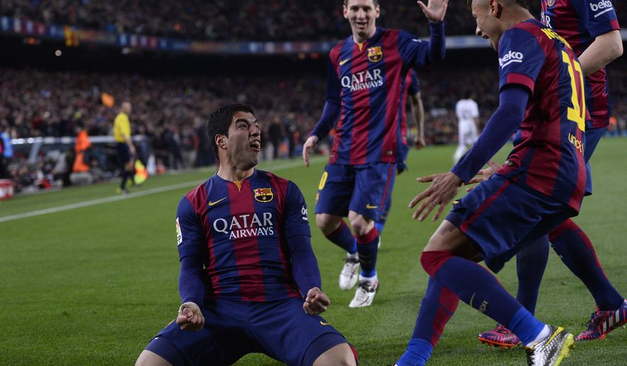 Barcelona's Luis Suarez, left, celebrates with team mates after scoring his team's second goal during a Spanish La Liga soccer match between FC Barcelona and Real Madrid at Camp Nou stadium, in Barcelona, Spain, Sunday, March 22, 2015. (AP Photo/Manu Fernandez)