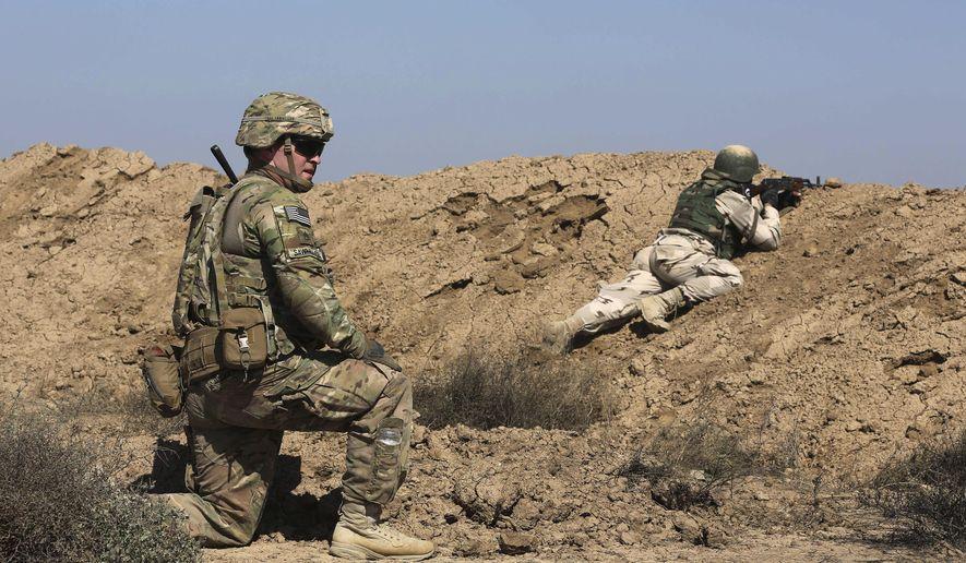 A U.S. soldier trains an Iraqi security forces member in a shooting drill in Taji, north of Baghdad, Iraq, Saturday, March 21, 2015. (AP Photo/Karim Kadim) ** FILE **
