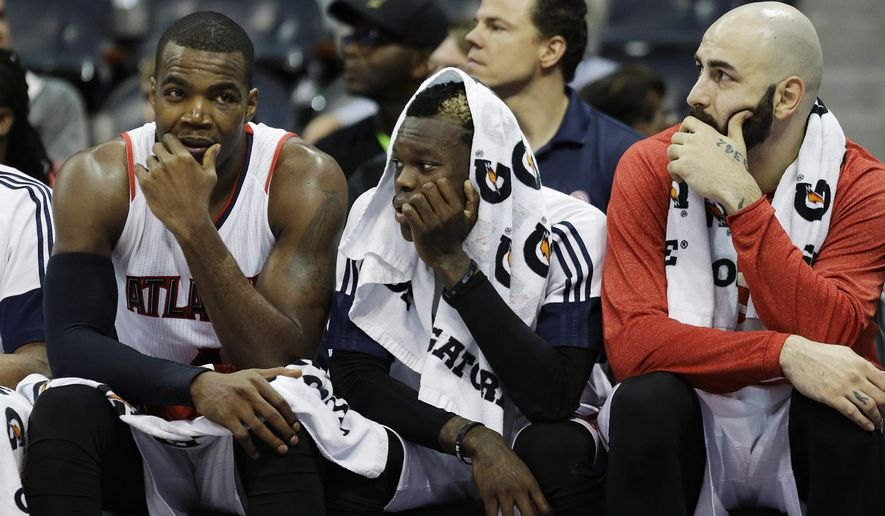 From left to right, Atlanta Hawks' Paul Millsap, Dennis Schroder, of Germany, and Pero Antic, of Macedonia, sit on the bench in the final minutes of an NBA basketball game against the San Antonio Spurs, Sunday, March 22, 2015, in Atlanta. (AP Photo/David Goldman)