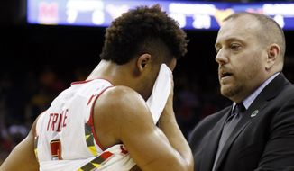 Maryland's Melo Trimble is checked by head trainer Matt Charvat in the second half of an NCAA tournament college basketball game against West Virginia in the Round of 32 in Columbus, Ohio, Sunday, March 22, 2015. (AP Photo/Paul Vernon)
