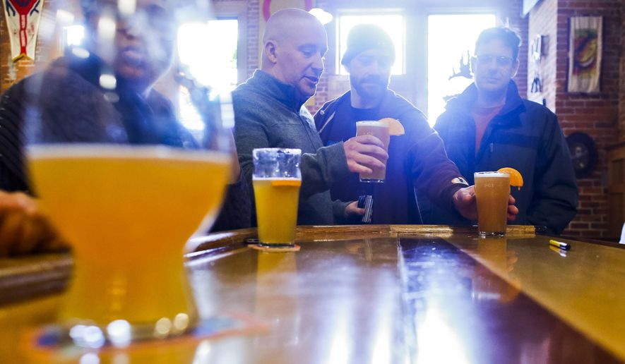 From left, Ross Schueller, Jeremy Berghorst and Scott Whycoff order a trio of Oberon Ales during Oberon Day at Bell's Eccentric Cafe in Kalamazoo, Mich., Monday, March 23, 2015. (AP Photo/Kalamazoo Gazette, Christian Randolph)