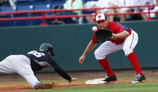 New York Yankees catcher John Ryan Murphy (66) dives back to first base as Washington Nationals first baseman Ryan Zimmerman (11) waits for the ball in the second inning of an exhibition spring training baseball game  Monday, March 23, 2015, in Viera , Fla. Murphy was safe on the play (AP Photo/John Bazemore)
