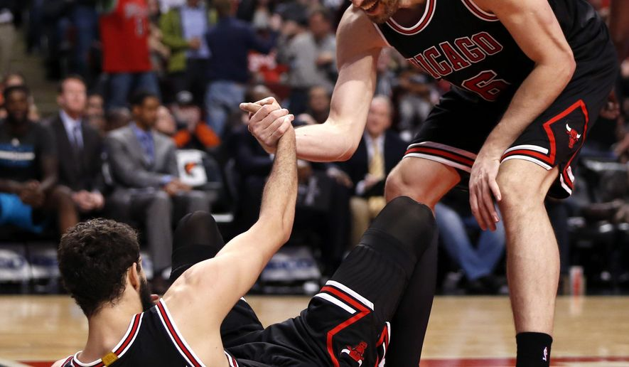 Chicago Bulls forward Pau Gasol, right, smiles as he helps up teammate Nikola Mirotic (44) during the second half of an NBA basketball game against the Charlotte Hornets Monday, March 23, 2015, in Chicago. The Bulls won 98-86. (AP Photo/Charles Rex Arbogast)