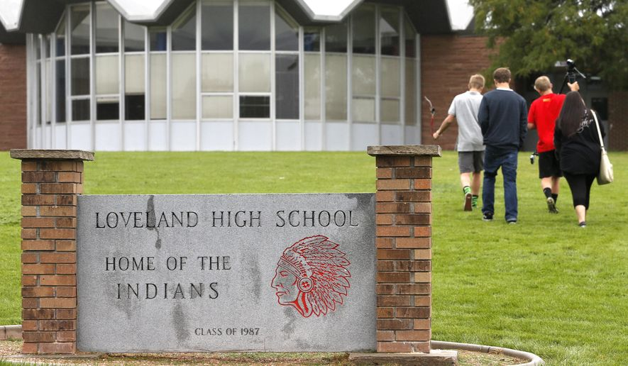 High school students walk into Loveland High School, past a sign at the entrance bearing the image of the school mascot, an American Indian, in Loveland, Colo., on Sept. 11, 2014. A bill up for its first hearing on March 23, 2015, in the Colorado House would require public schools with American Indian mascots or logos to get permission from a panel of nine Native Americans. (Associated Press) **FILE**
