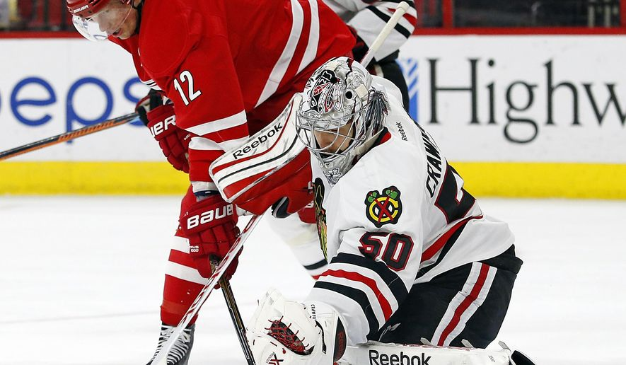 Chicago Blackhawks goalie Corey Crawford (50) blocks the shot of Carolina Hurricanes' Eric Staal (12) during the second period of an NHL hockey game Monday, March 23, 2015, in Raleigh, N.C. (AP Photo/Karl B DeBlaker)