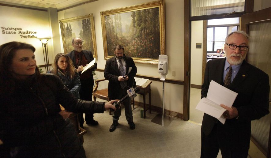 Thomas Shapley, Deputy Director, Communications, Washington State Auditor distributes a prepared statement from Washington State Auditor Troy Murphy in Olympia, Wash., March 23, 2015. Kelley returned to work Monday following a week where his home was raided by federal agents and his office turned over records that were subpoenaed by the Justice Department. (AP Photo/The Olympian, Steve Bloom)