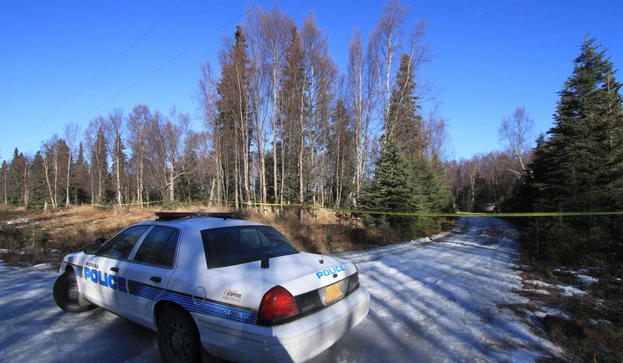 A Kenai Police Department patrol car parked on Alpine Avenue blocks an unnamed trail on Monday, March 23, 2015, in Kenai, Alaska. Human remains of four people were found Saturday night about 15 yards off the trail and Kenai police say evidence indicates they were members of family that has been missing since May.  (AP Photo/Dan Joling)