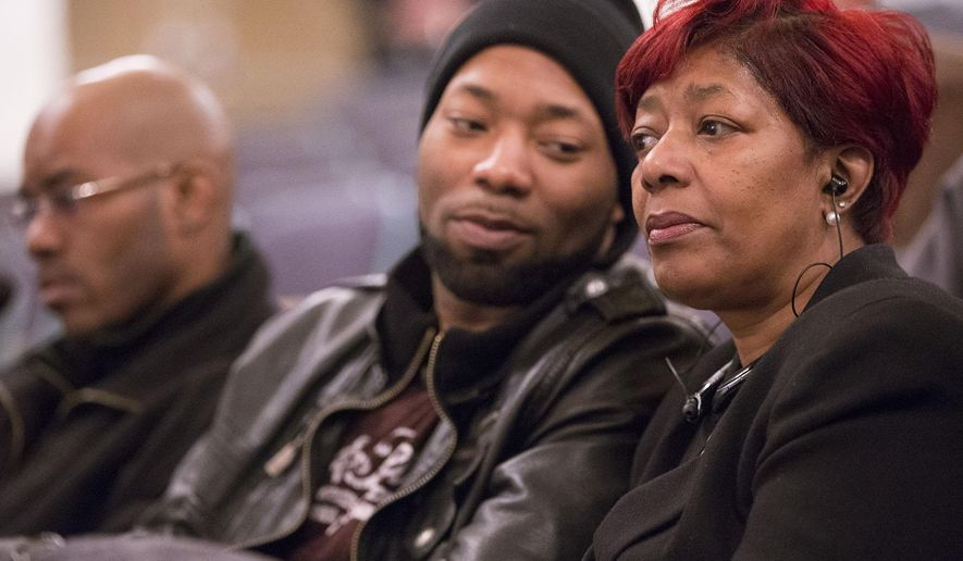 Maria Hamilton, right, mother of Dontre Hamilton, listens during a disciplinary appeal for fired police officer Christopher Manney before a panel of three Fire and Police Commission members at Centennial Hall  Monday, March 23, 2015 in Milwaukee, Wis. Manney, who was fired after the fatal on-duty shooting of Dontre Hamilton, has maintained that he has done nothing wrong. With her, are Dontre Hamilton's brothers Dameion Perkins, center, and Nate Hamilton. (AP Photo/Milwaukee Journal-Sentinel, Mark Hoffman)