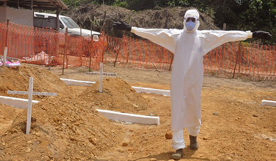 In this photo taken on Wednesday, March 11, 2015, a health worker holds up his arms after he and others buried a person that they suspect died form the Ebola virus at a new graveyard on the outskirts of Monrovia, Liberia. One year after the World Health Organization declared the Ebola outbreak, vaccine trials are under way in Liberia and Guinea. Sierra Leone will start a trial later this month. (AP Photo/ Abbas Dulleh)