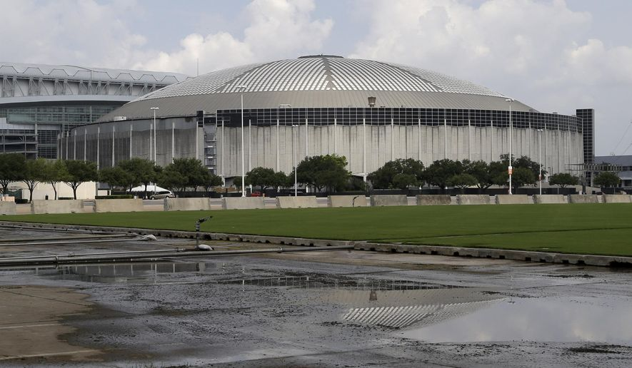 FILE - In this July 30, 2014, file photo, the Houston Astrodome is reflected in a puddle in Houston. A proposal to turn the iconic but shuttered Astrodome into a massive indoor park and build a tree-lined green space around the structure could cost nearly $243 million, according to a report released Monday, March 23, 2015, by a nonprofit research group focused on land use. (AP Photo/Pat Sullivan, File)