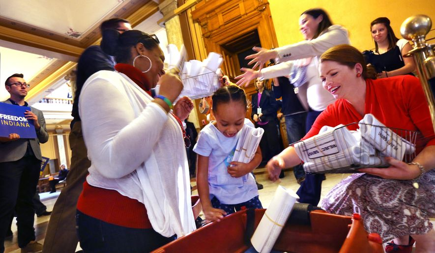 Patience Alexander, 5, center, daughter of Angie Alexander, left, and Cynthia Alexander (not shown), was recruited by Freedom Indiana to deliver two wagonloads of letters, about 10,000 in all, from opponents of the Religious Freedom Restoration Act to the office of Indiana House of Representatives Speaker Brian Bosma, R-Indianapolis, and accepted by Tory Flynn, right, director of communications for the Indiana House Republicans, at the Indiana Statehouse in Indianapolis on Monday, March 23, 2015. Morgan Perrill (above Flynn), staff director and legislative assistant for Bosma, helped accept the letters. Supporters say the legislation would protect religious freedoms, but opponents say it would allow discrimination against gays and lesbians. The Indiana House today is expected to vote on the legislation on Monday. (AP Photo/The Indianapolis Star, Charlie Nye)