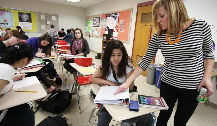 In this Thursday, March 19, 2015 photo, Jada Callahan, right, discusses an assignment with junior Jailene Rodriguez in an Intro to Sociology 101 college course at Middleton High School in Middleton, Wis. Wisconsin school districts will have to begin covering the costs of high school courses that earn students college credit after the University of Wisconsin System decided it couldn't continue paying for them. (AP Photo/Wisconsin State Journal, Amber Arnold)