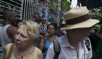 Tourists visit the Hamel Alley as a Cuban woman smokes a cigar in the background, in Havana, Cuba, Sunday, March 22, 2015. Tourism to Cuba is up sharply in the months since Washington and Havana announced in December that they would move toward a historic rapprochement. (AP Photo/Desmond Boylan)