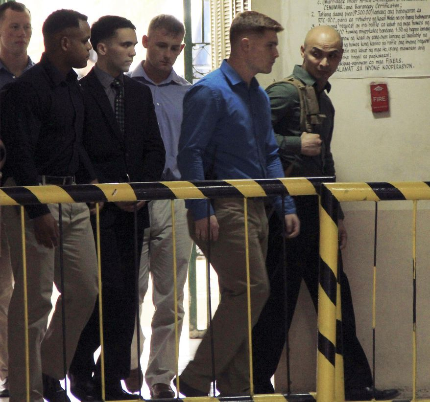 "U.S. Marine Pfc. Joseph Scott Pemberton, third left, the suspect in the Oct.11, 2014 killing of Filipino transgender Jennifer Laude at the former U.S. naval base of Subic, northwest of Manila, is escorted into the courtroom for his scheduled trial Monday, March 23, 2015 at Olongapo city, Zambales province, northwest of Manila, Philippines. Pemberton was tagged as the suspect in the killing which the protesters termed as a ""hate crime"" against LGBT (Lesbian, Gay, Bisexual and Transgender) Filipinos. (AP Photo/Jun Dumaguing)"