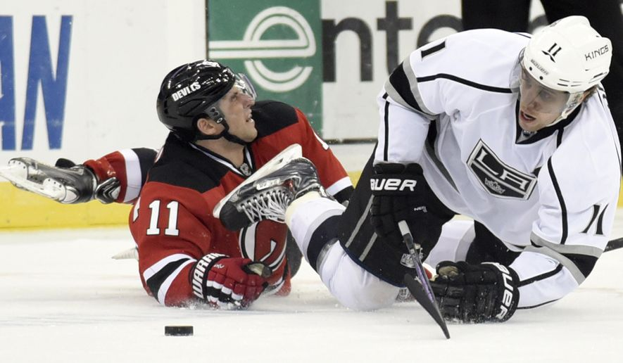 Los Angeles Kings' Anze Kopitar, right, is tripped by New Jersey Devils' Stephen Gionta during the first period of an NHL hockey game Monday, March 23, 2015, in Newark, N.J. (AP Photo/Bill Kostroun)