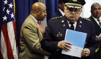 Philadelphia Police Commissioner Charles Ramsey holds a newly released report during a news conference Monday, March 23, 2015, in Philadelphia. Poor training has left Philadelphia police officers with the mistaken belief that fearing for their lives alone is justification for using deadly force, the Justice Department said Monday in a review of the city's nearly 400 officer-involved shootings since 2007.  (AP Photo/Matt Rourke)