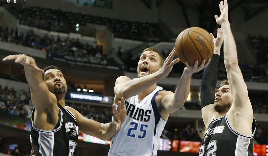 Dallas Mavericks forward Chandler Parsons (25) attempts a shot as San Antonio Spurs forwards Tim Duncan, left, and Tiago Splitter (22) defend during the first half of an NBA basketball game, Tuesday, March 24, 2015, in Dallas. (AP Photo/Brandon Wade)