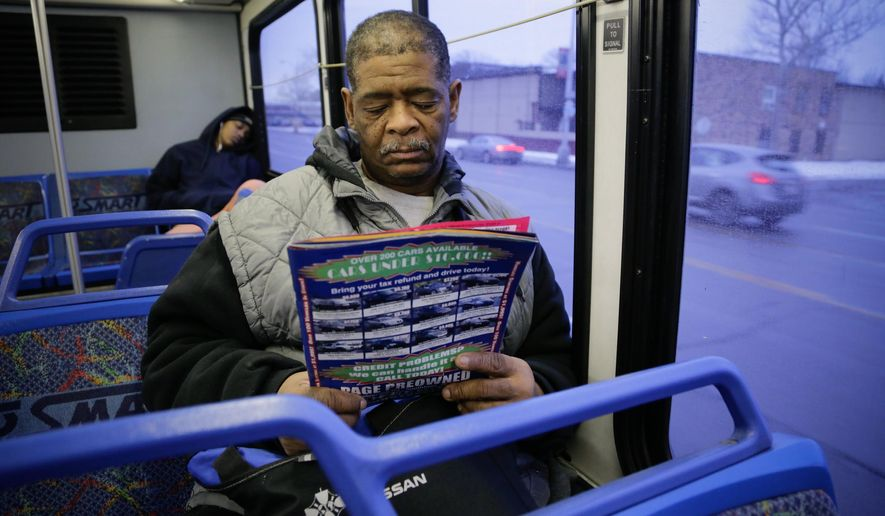 File- This Jan. 29, 2015, file photo shows James Robertson 56, of Detroit looking over ads for used cars while riding the SMART bus as a part of his commute to work. A Brookings Institution report out Tuesday, March 24, 2015, finds the number of jobs within typical commuting range dropped 7 percent between 2000 and 2012 in major U.S. metropolitan areas. (AP Photo/Detroit Free Press, Ryan Garza) DETROIT NEWS OUT; TV OUT; MAGS OUT; NO SALES; MANDATORY CREDIT DETROIT FREE PRESS